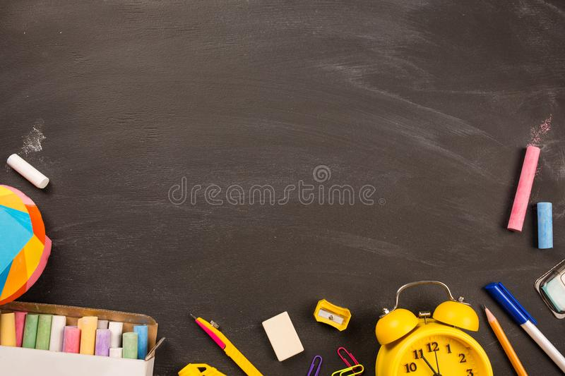 Bright office supplies, yellow alarm clock on black chalkboard top view, copy space. concept: back to school. School`s out, school holidays, teacher`s day stock images