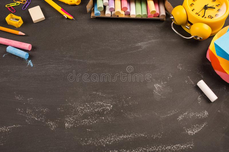 Bright office supplies, yellow alarm clock on black chalkboard top view, copy space. concept: back to school. School`s out, school holidays, teacher`s day stock photography