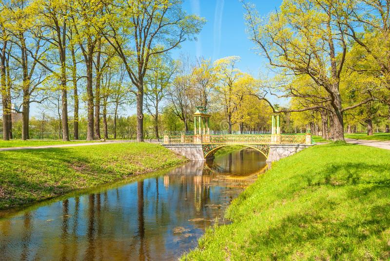 In spring park. Bright old bridge in spring park royalty free stock photography