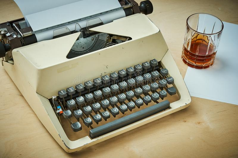 Bright old typewriter with gray keys, paper and a glass of alcohol stock photo