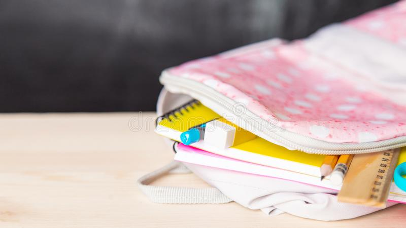Bright open school bag with school supplies lies on a desk against the background of a school blackboard stock photos