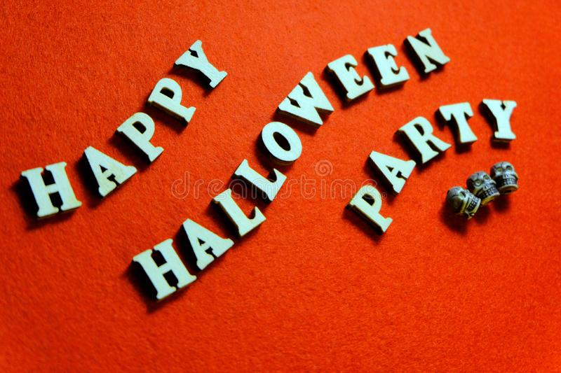 Inscription HAPPY HALLOWEEN PARTY made of wooden letters. Bright orange background. Three skulls lie next to the words in the form. Bright orange background stock images
