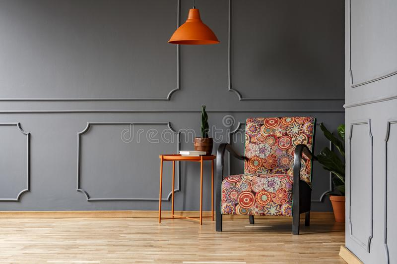 Bright orange ceiling light above a boho style armchair in an elegant living room interior with molding on gray walls and copy sp stock images