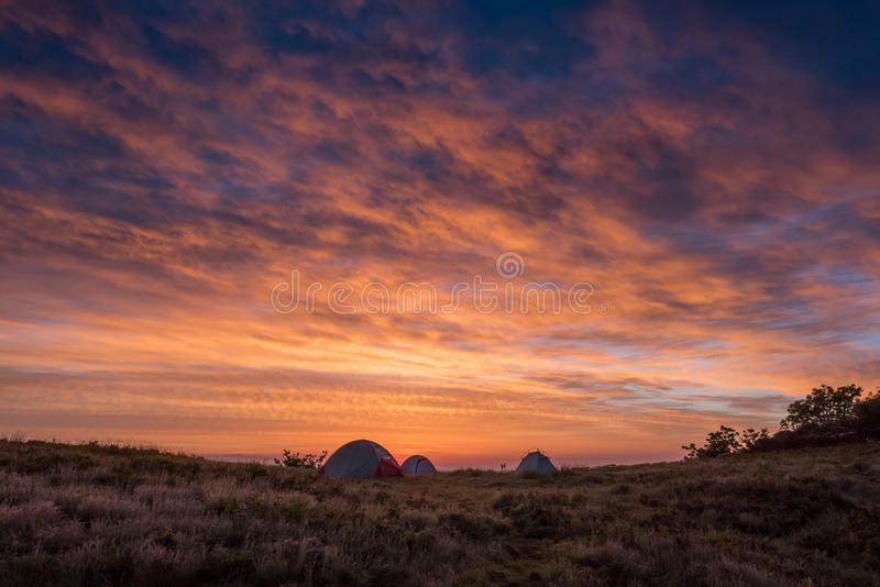 Bright Orange Clouds Glow Above Three Tents royalty free stock photography