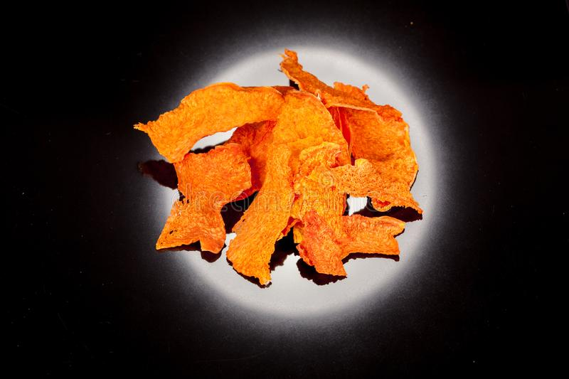 Bright, orange, crunchy, crisp snack of ripe and sweet pumpkin on a black backgroun. For culinary design stock photo