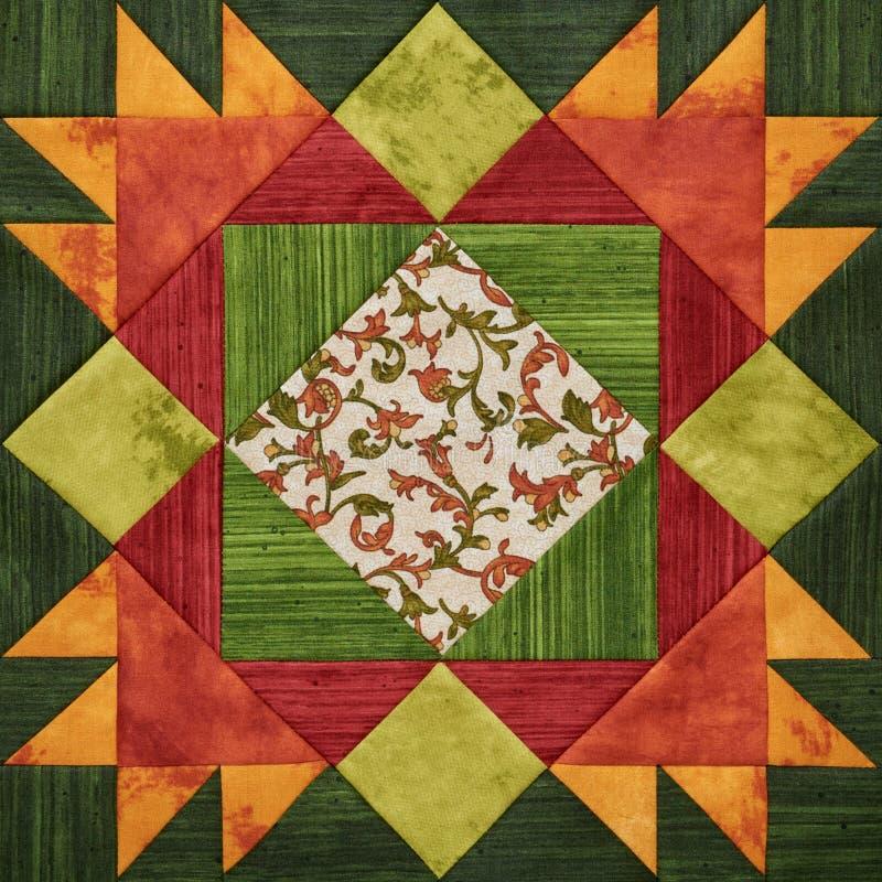 Bright orange-green geometric patchwork block from pieces of fabrics royalty free illustration