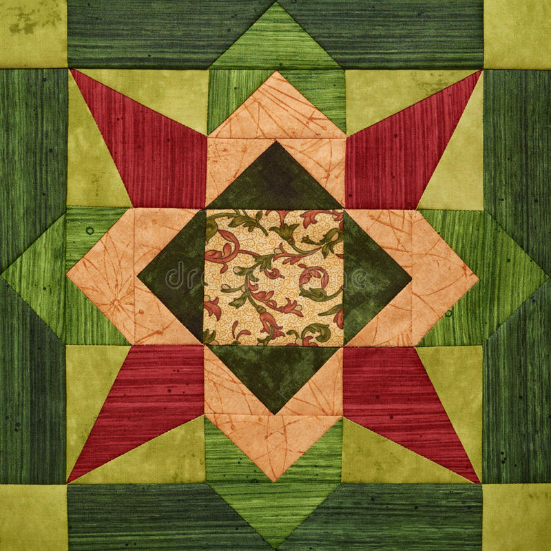 Bright orange-green geometric patchwork block from pieces of fabrics, detail of quilt stock image
