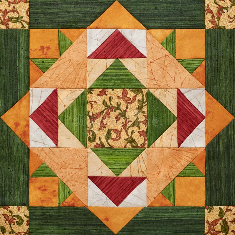 Bright orange-green geometric patchwork block from pieces of fabrics royalty free stock image