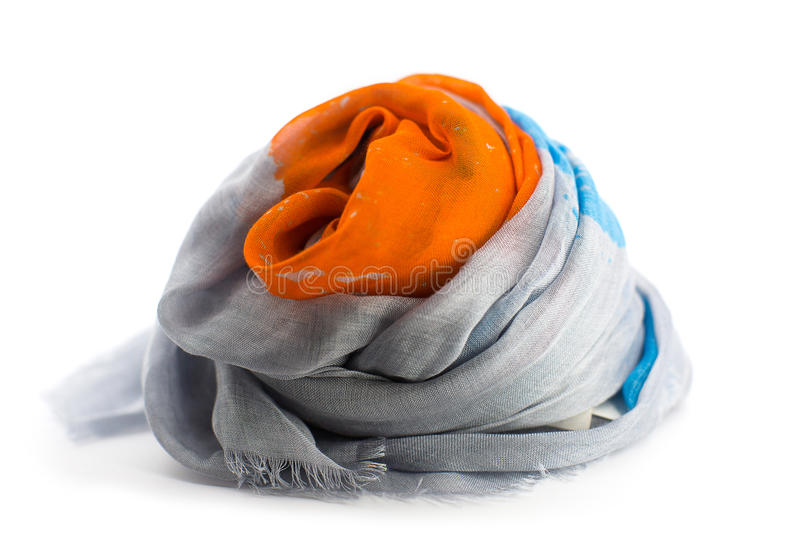Bright orange, grey, blue female scarf close-up. On the table with white background stock image