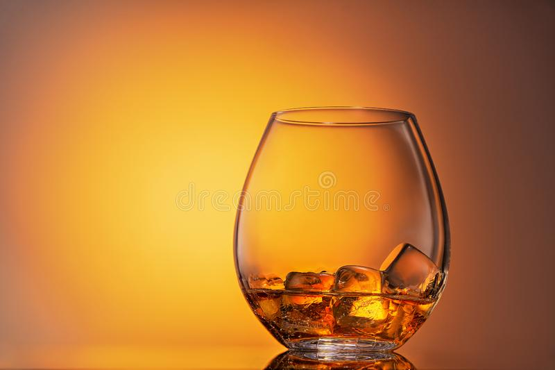 Glass of scotch whiskey and ice on a white background royalty free stock photography