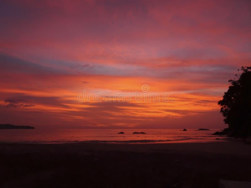 Bright orange, pink, purple sunset colors over the calm sea stock images