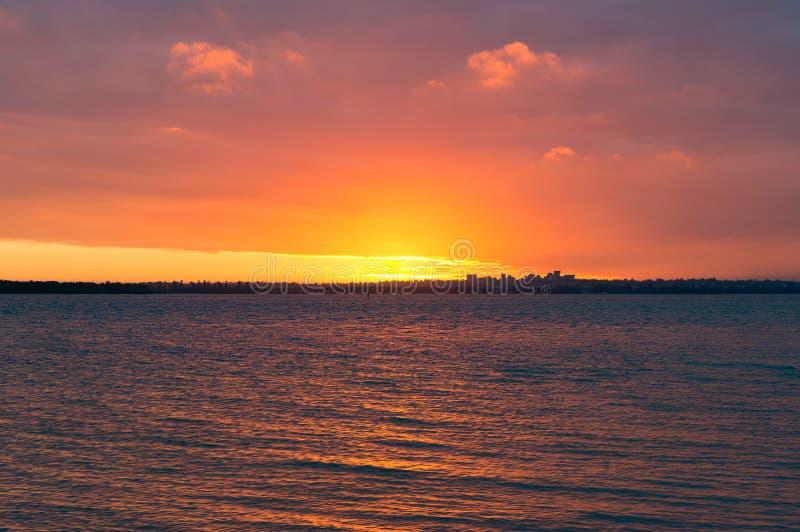Bright orange red sunset sky over water stock photo