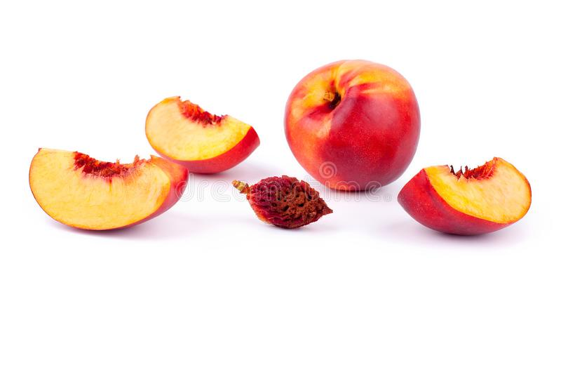 Peach whole and cut into four quarters on a white background isolated close up stock photo