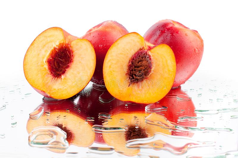 Peaches whole and cutted into two halves in water drops on white background isolated close up. Bright orange ripe peaches whole and cut into two halves and with royalty free stock images