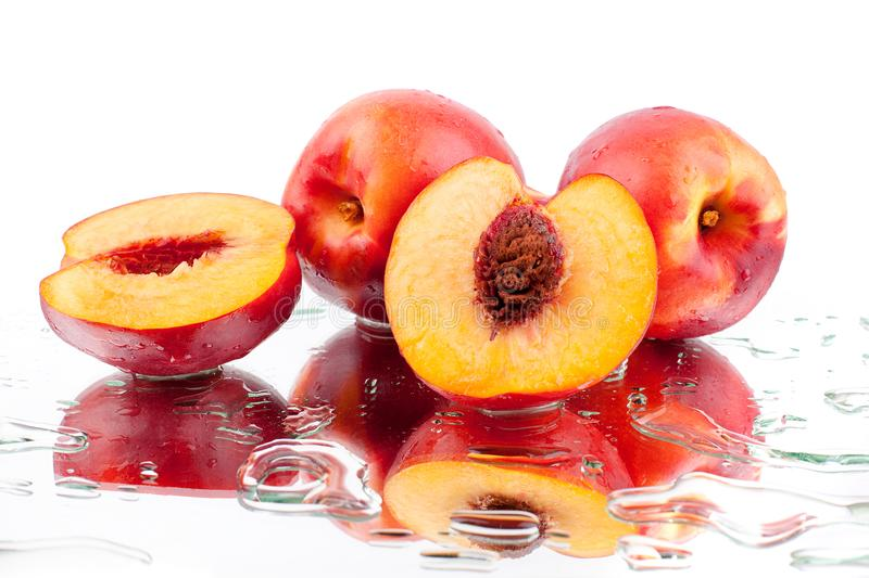 Peaches whole and cutted into two halves in water drops on white background isolated close up. Bright orange ripe peaches whole and cut into two halves and with royalty free stock photography
