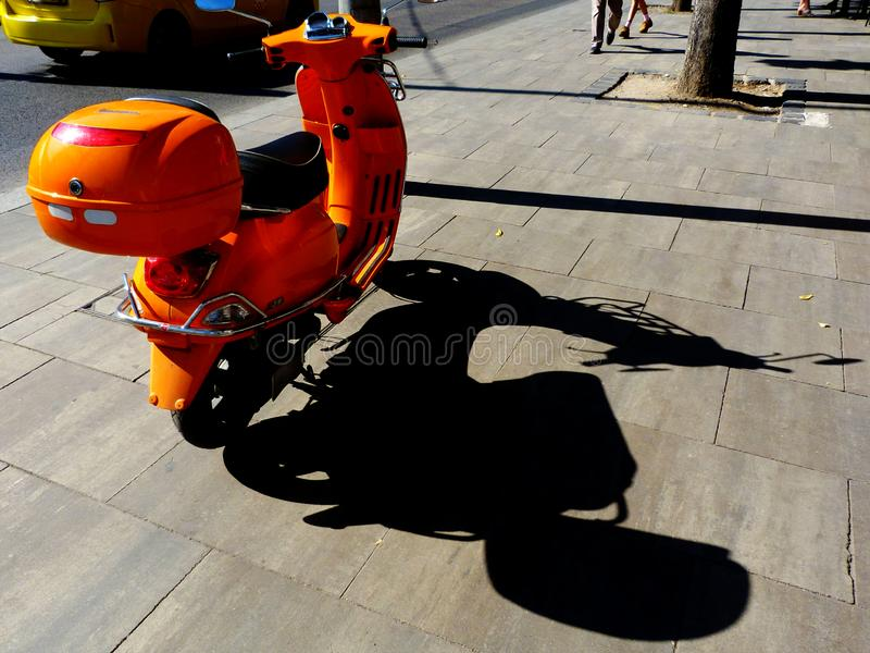 Bright orange scooter parked on stone sidewalk with strong shadow. Bright orange scooter with storage box parked on stone paved sidewalk with strong shadow in royalty free stock photo