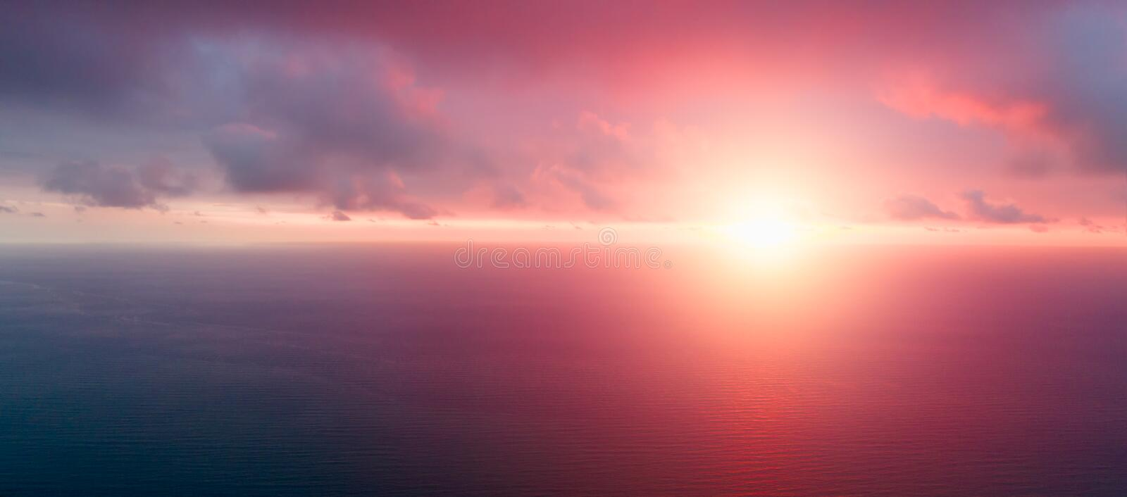 Bright orange sky and light of the sun. Sky background on sunset. Nature composition. Panoramic sunset sky background. Sunrise sky. With lighted clouds. Beauty stock photography
