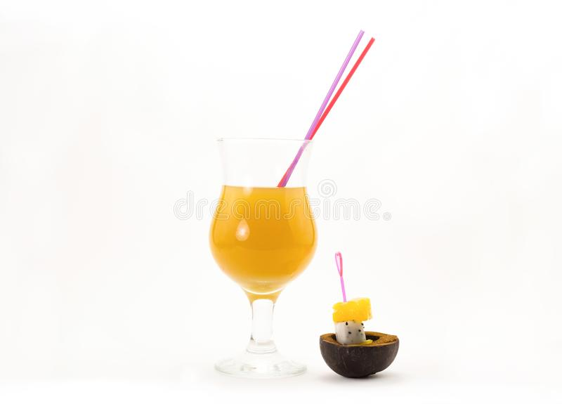 Bright orange sunny cocktail tube and two exotic fruit and yellow melon on skewers pitah eco bowl royalty free stock images