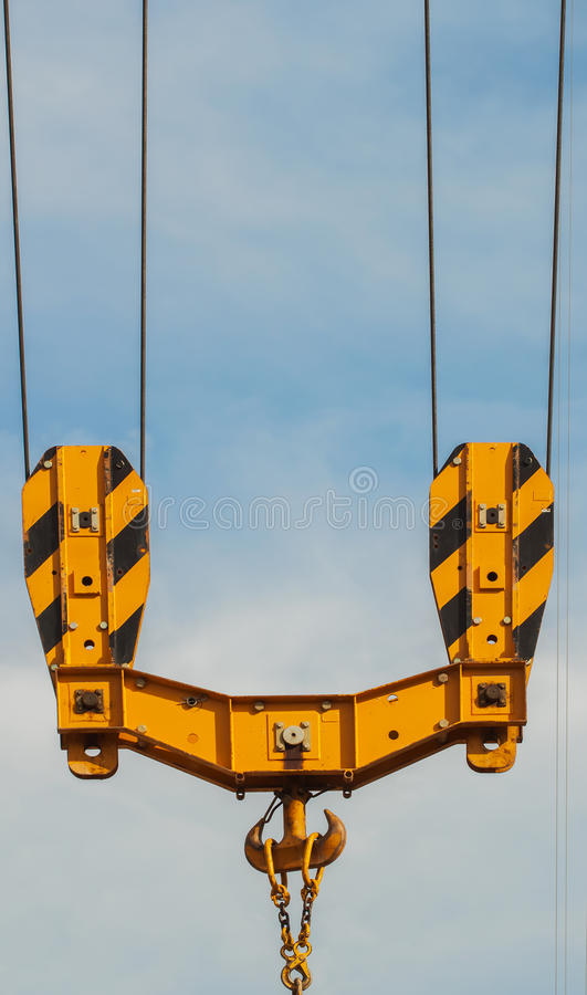 Bright orange tower crane against of blue sky , hook detail, construction concept royalty free stock photography