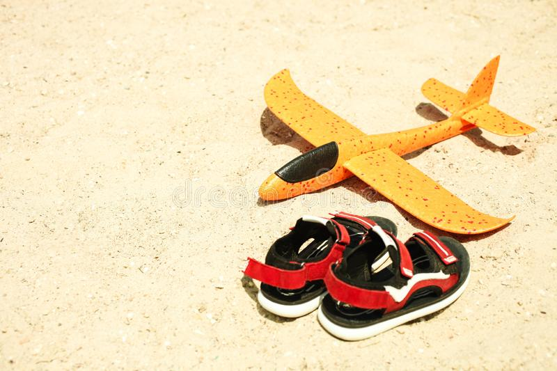 Toy foam airplane and children`s red sandals. Bright orange toy foam airplane and children`s red sandals lies on sand on sunny summer day. Concept summer stock image