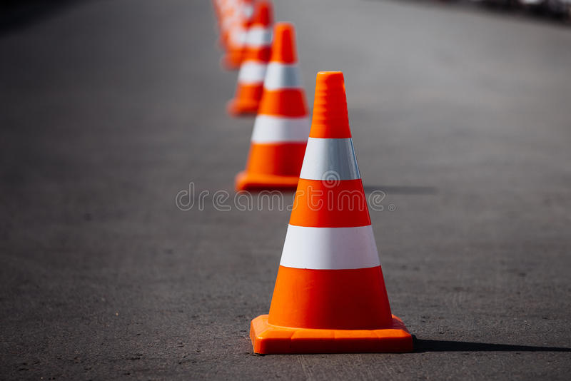 Bright orange traffic cones. Standing in a row on dark asphalt stock images