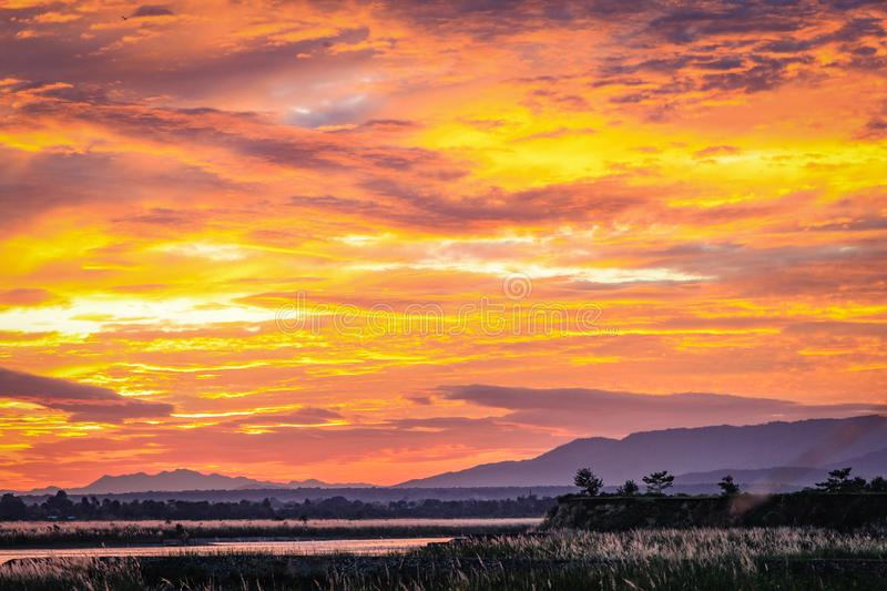Bright orange and yellow sunset over flat river with a plateau and small trees on the right stock images