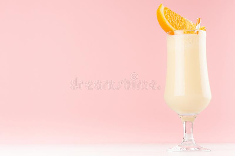 Bright oranges milkshake in elegance glass with slices orange on white wooden table and pastel light pink wall. royalty free stock photo