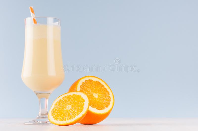 Bright oranges milkshake with slices citrus, striped straw on white wooden table and pastel light blue wall. royalty free stock photos