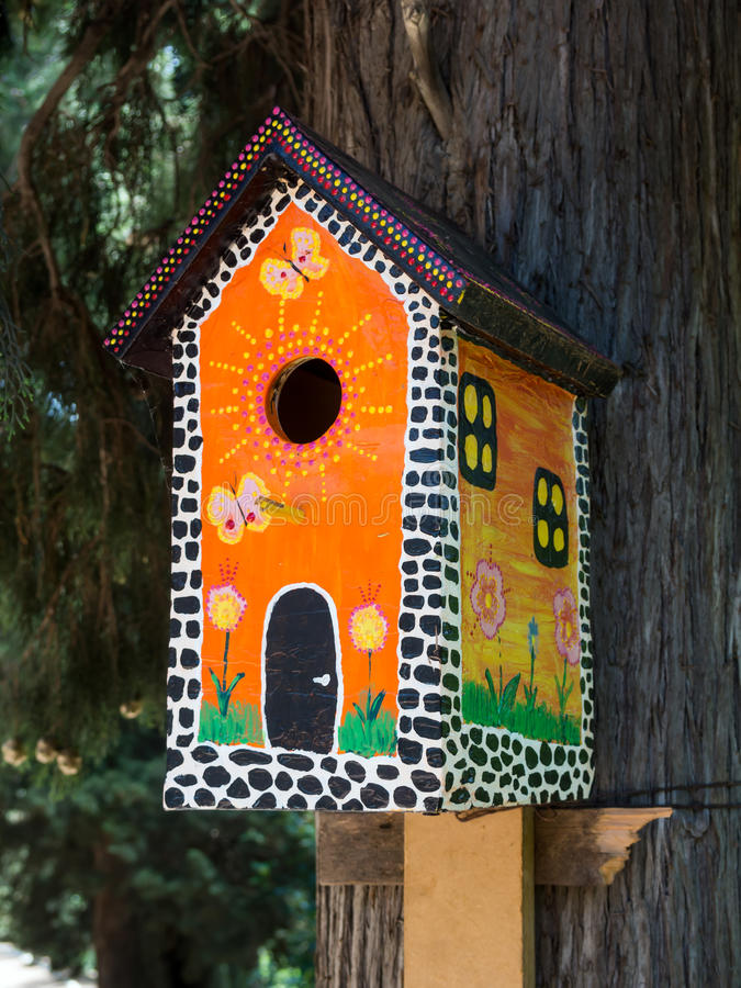 Bright, painted under the multi-storey house, birdhouse on a tree trunk.  stock image