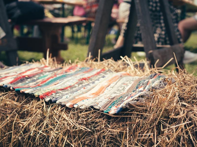 The bright patchwork rug lying on a bale of straw. Craft decoration at local summer country festival royalty free stock photo