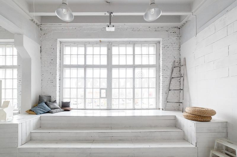 Bright photo studio interior with big window, high ceiling, white wooden floor stock photo