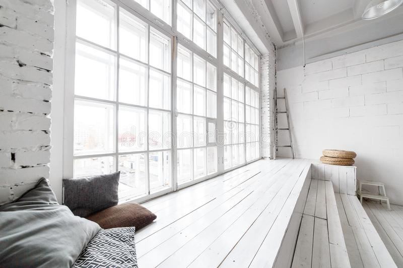 Bright photo studio interior with big window, high ceiling, white wooden floor royalty free stock images