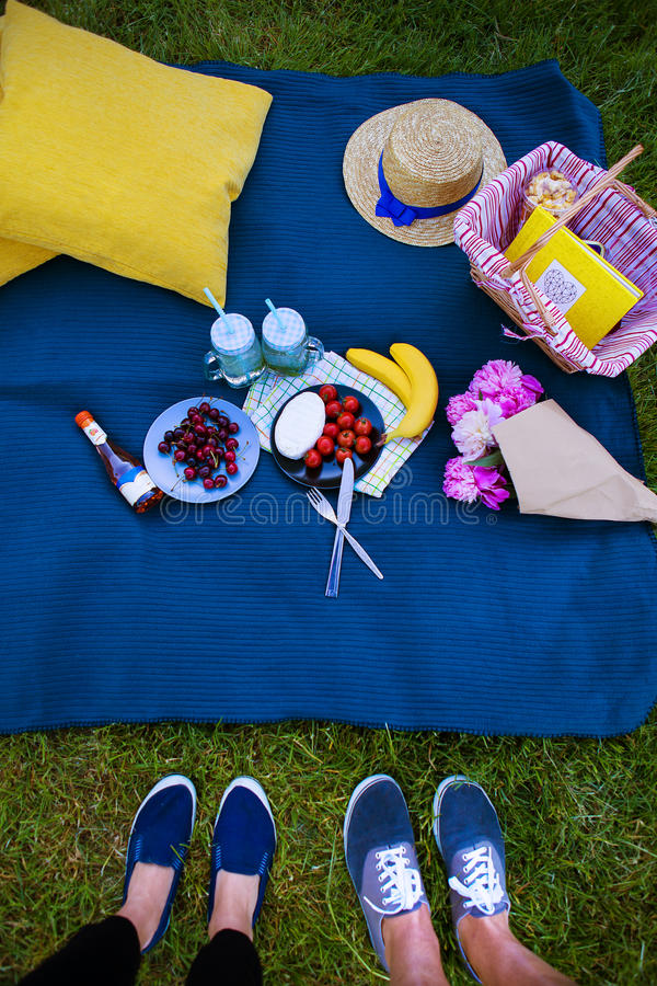 Bright picnic on the nature-flowers, delicious food, a loving couple. stock photography