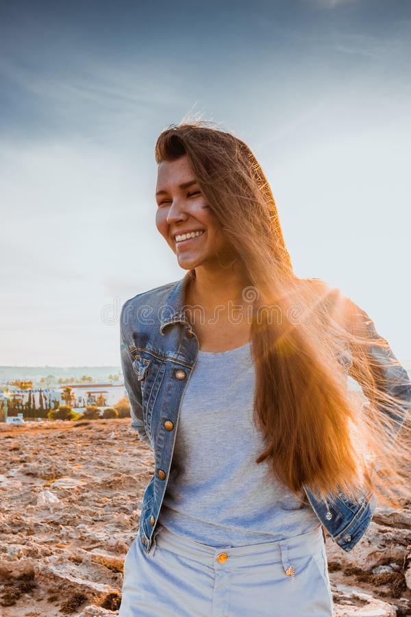 Bright picture of laughing woman on the beach. backlight sunlight in backgroiund. beautiful caucasian young female model royalty free stock photography