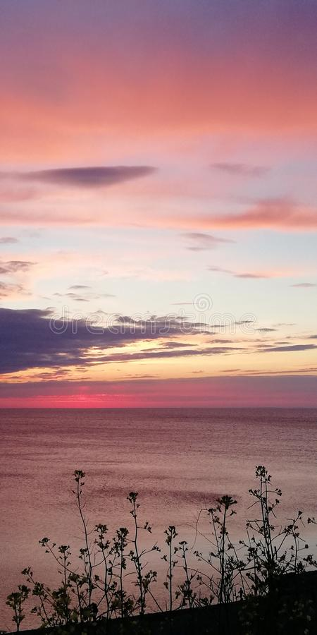 Bright picturesque contrasting background. Sea evening sunset landscape in pink, red, gold and blue tones stock photos