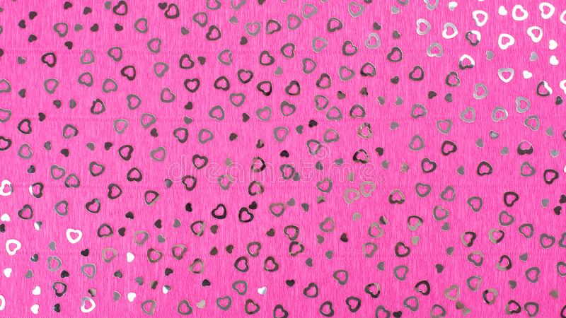 Bright pink crepe paper background. Bright pink crepe paper background with hearts sequins stock photo