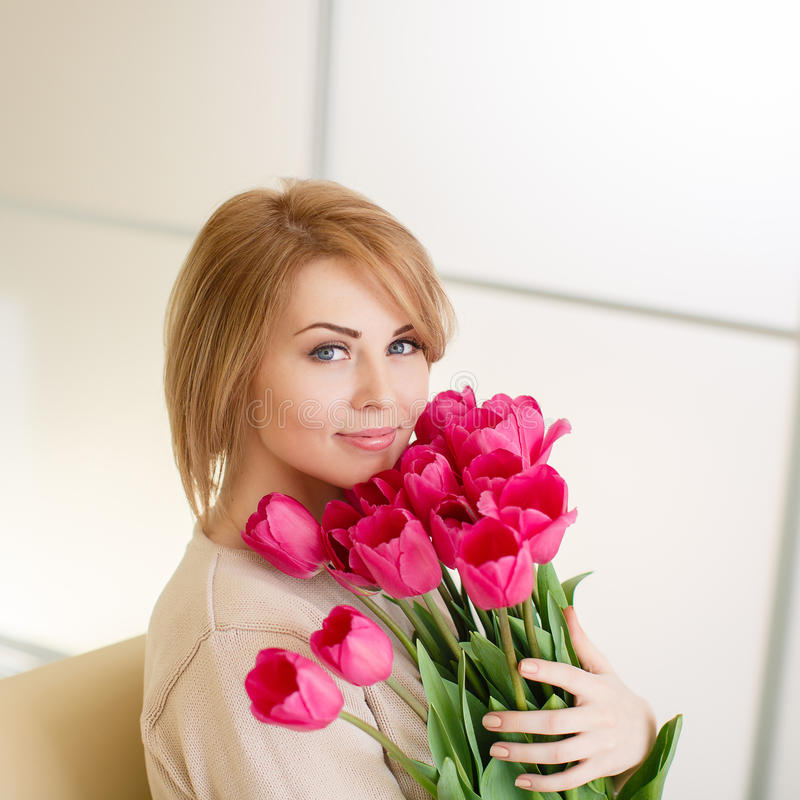 Bright pink flowers in girl's hands. Beautiful young blond woman with tulip bouquet. Spring portrait. Bright pink flowers in girl's hands. At home. Interior stock image