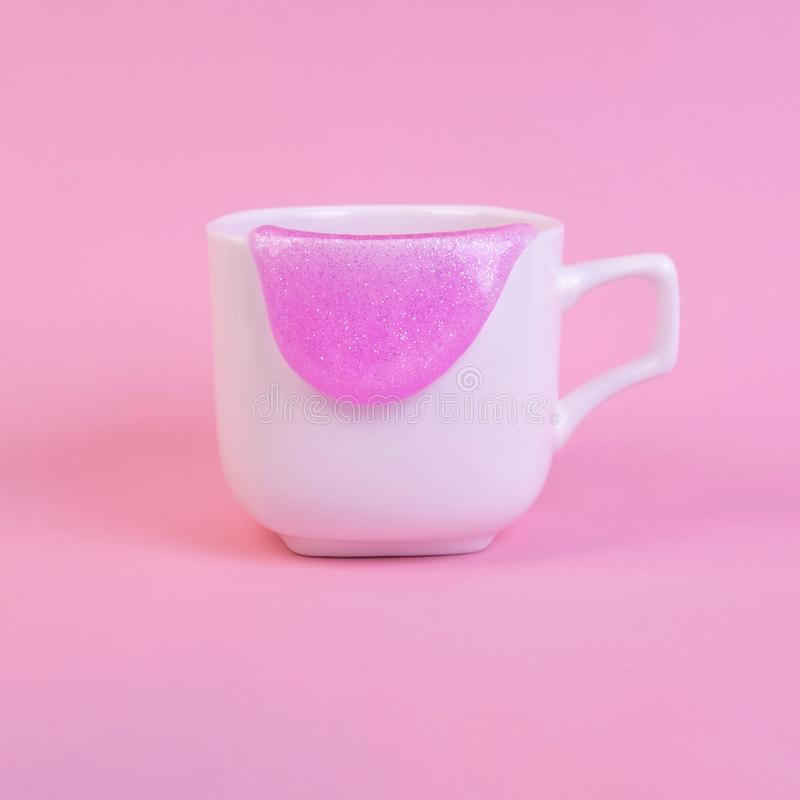 Bright pink glitter slime. Comes out of mug. White cup on pink background. Art neon surrealism and minimalism concept stock image