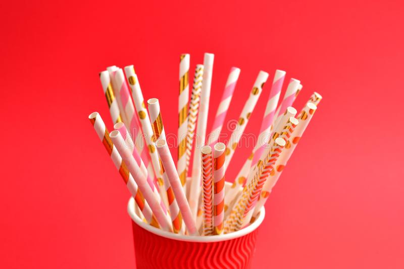 Bright pink and golden tubules in a paper cup. Copy space. Top view royalty free stock image