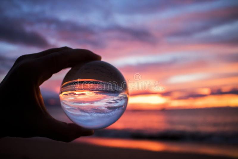 Bright Colorful Sunset over Ocean Captured in Glass Ball royalty free stock photography