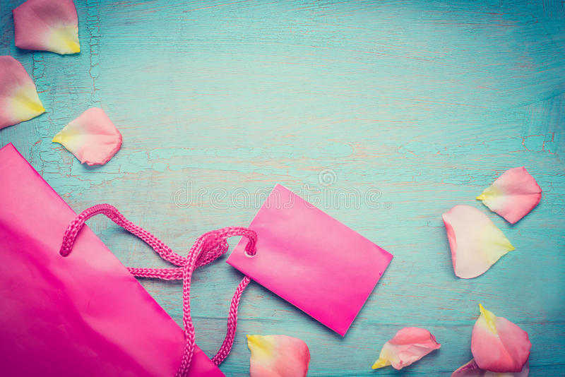 Bright pink paper shopping bag with flowers petal on blue turquoise shabby chic background, top view, place for text, border. Sum. Mer bargain sale. Retro styled royalty free stock photos