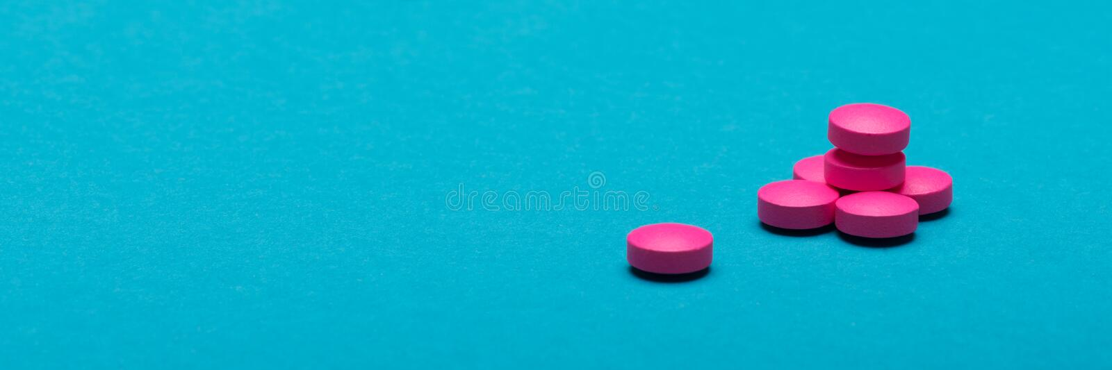 Bright pink pills on dark blue coloured background. Medication and prescription pills web banner. stock photo