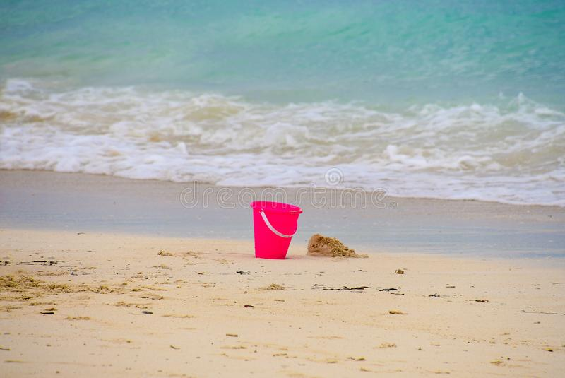Pink toy beach pail in sand royalty free stock photography