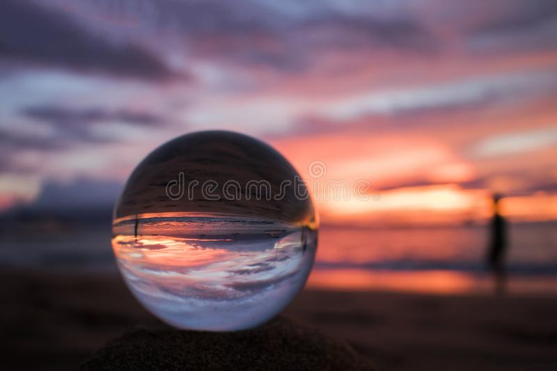 Bright Pink and Purple Seascape Sunset over Ocean with Glass Ball royalty free stock photos