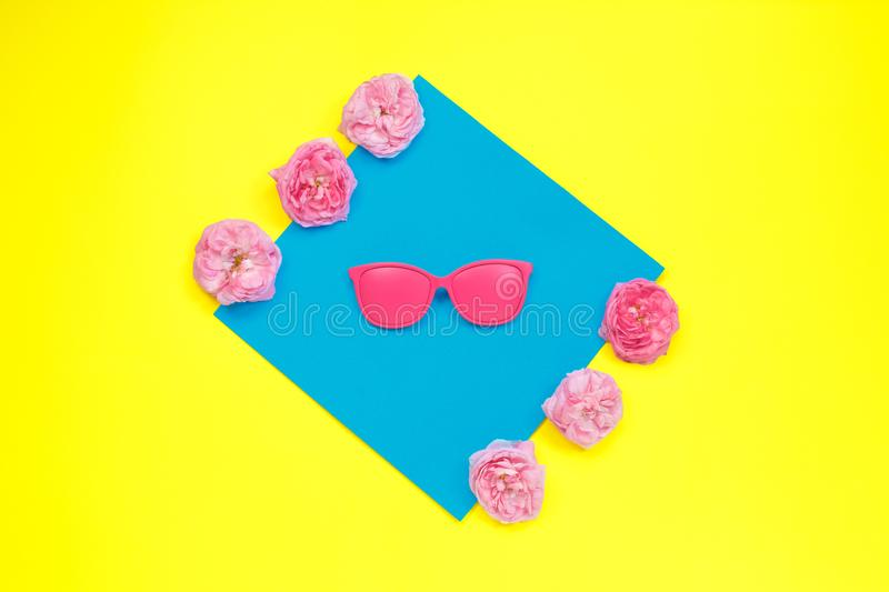 Bright pink sunglasses and pink roses in vibrant bold color on dual background. fashion concept. minimalism. Flat lay, top view,. Copy space Summer concept royalty free stock photo