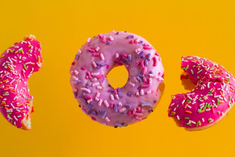 pink sweet donuts with sprinkles on vibrant yellow background royalty free stock photo