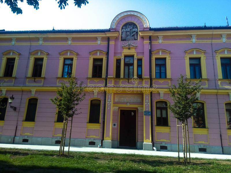 Bright pink and yellow rustical building in a city. Park royalty free stock photo