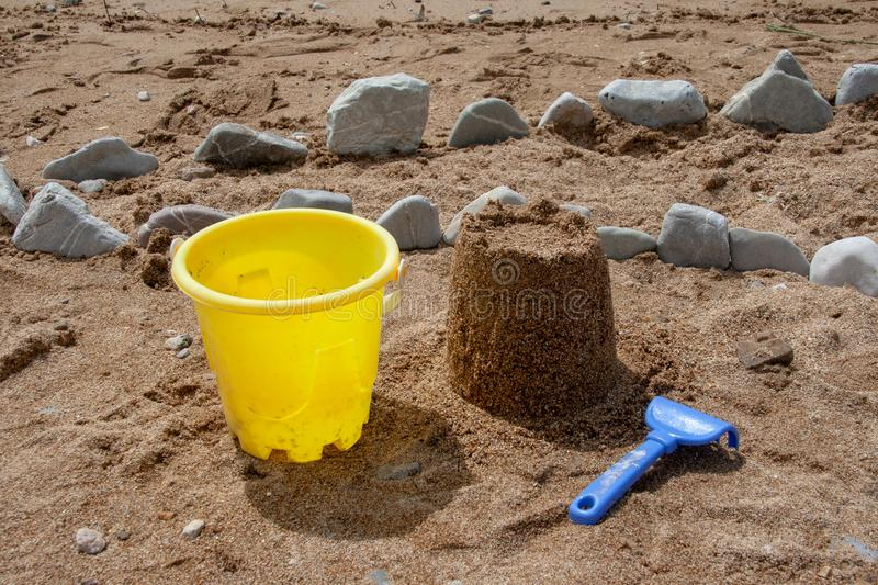 Bright plastic children`s toys in the sand. Concept of beach recreation for children. stock photos