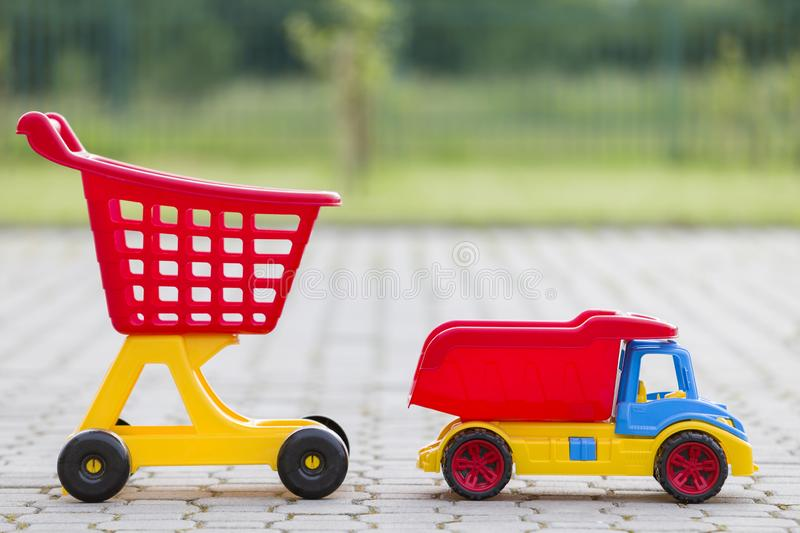 Bright plastic colorful toys for children outdoors on sunny summer day. Car truck and shopping pushcart royalty free stock images