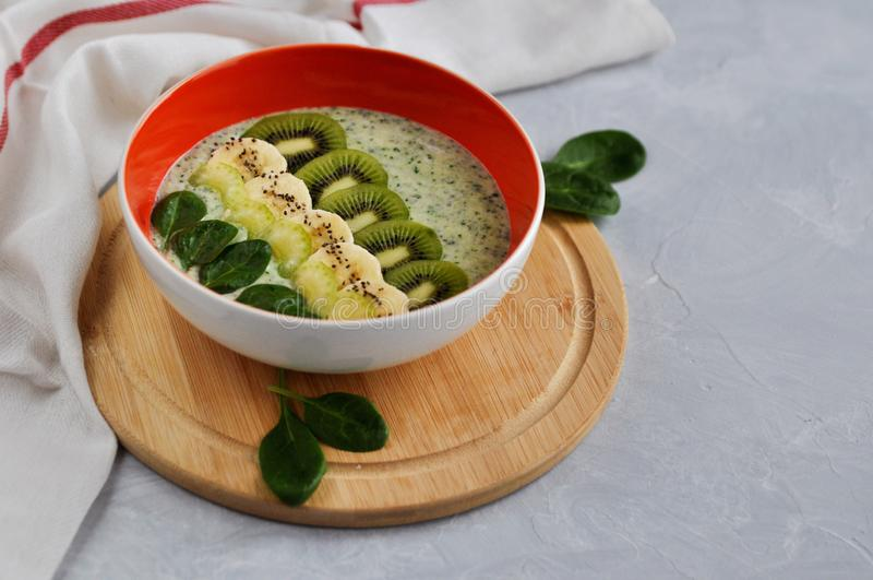 Bright plate with a healthy Breakfast power bowl made of natural yogurt, Chia seeds, banana, kiwi, celery and spinach on a gray stock image